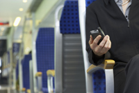 Man in train with phone in hand